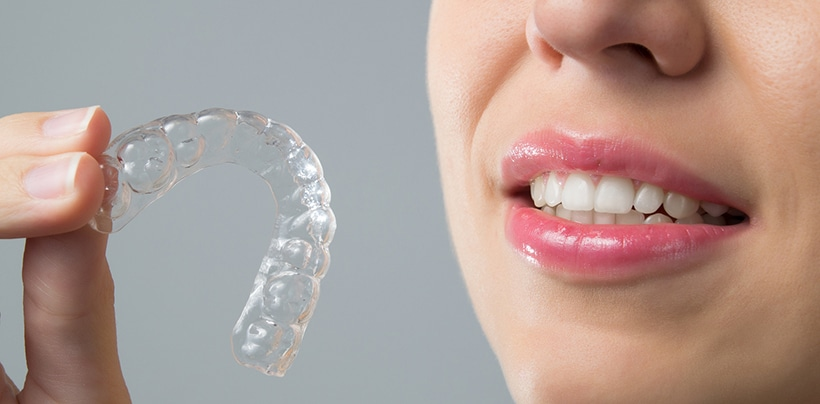 smiling woman with an Invisalign aligner
