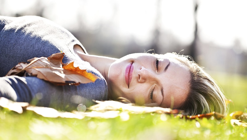 Serene woman is resting on the meadow.