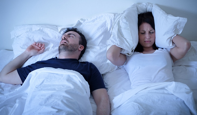 A man is keeping his wife awake beacuse of his sleep apnea and snoring