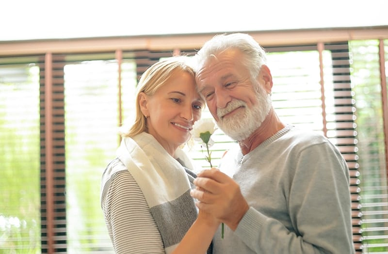 Portrait of an elderly couple hold a flower in their hands, relaxing in their home. Eventhough they may have bone loss in their gums doesn't mean they can't qualify for dental implants.