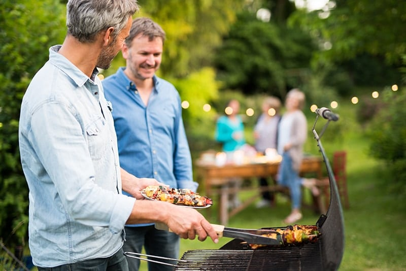 In a summer evening, two men in their forties prepares a barbecue for friends gathered around a table in the garden. Unfortunately, some of these foods are terrible for your teeth. They can do serious damage and increase your risk of tooth decay and damage.
