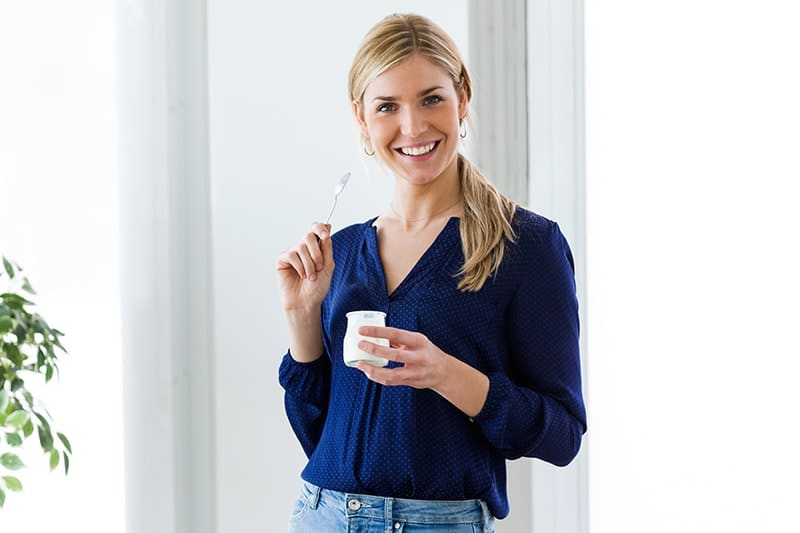 Beautiful woman looking at camera while eating yogurt at home. Eating this and other dairy products like rich in calcium can help build stronger bones - that includes your teeth.