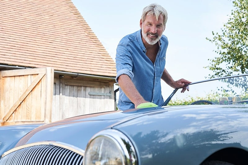 Mature Man Polishing Restored Classic Sports Car Outdoors At Home. A recent study released by cars.com shows that Americans service their cars at an average of two thirds more often than they go to the dentist for routine care. Are you taking better car of your car than your teeth?