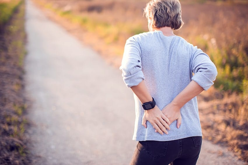 Woman walking on trail experiences lower back pain