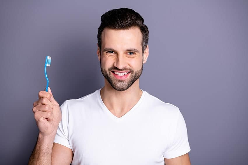 closeup of a man smiling and showing off her toothbrush